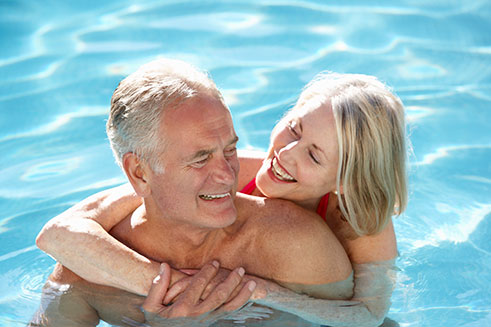 Couple swimming in solar heated pool